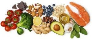 Verschiedene gesunde und vitaminreiche Lebensmittel einer Ernährungsberatung. Tomaten, Brokkoli, Rosenkohl, Ingwer, Zitrone, Bohnen, Avocado, Olivenöl, Knoblauch, Spinat, Lachs, Haferflocken, Heidelbeeren, Baumnuss, Mandel, Schokolade